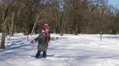 wintertime : Little Caucasian girl having fun playing in the snow in winter city park