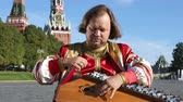 songster : The musician in traditional Russian clothes plays an old Russian musical instrument gusli on the background of the Kremlin on red Square. Moscow, Russia