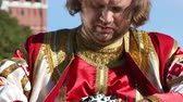 songster : Folk minstrel in traditional Russian clothes plays an old Russian musical instrument gusli on the background of the Kremlin on red Square. Moscow, Russia Stock Footage