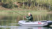 inflável : Senior fisherman fishing on the lake with an inflatable boat and caught fish