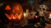 Autumn still life with Halloween pumpkins, skull, old books, maple leaves, vintage bottles and candles on old wooden background