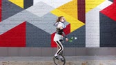 coringa : Girl clown with white rose riding a unicycle outdoors Vídeos