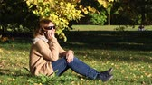 A young woman sitting on the leaves in the autumn park and talking on a mobile phone 무비클립