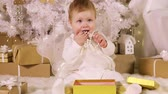 Pretty little girl (eight months of age) in a white dress sitting under a Christmas tree with gifts 무비클립