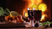 Two glasses of mulled wine (gluhwein) and a plate of fruit on the background of a burning fireplace 무비클립