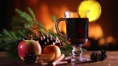 A glass of mulled wine (hot wine) with fruit and pine branches on the background of a burning fireplace