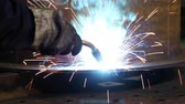kaynakçı : Bright sparks from welding equipment while the welder is working in an industrial shop