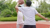 aliciamento : Asian kid doing shot fake when playing basketball with father outdoor in playground in slow motion Stock Footage