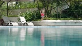 saneamento : Asian teenager running & jumping into swimming pool in landscaped garden in summer