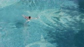 sanitation : High angle view of Asian teenager swimming alone in blue pool in summer