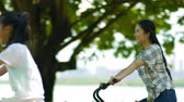 à beira do lago : asian mother & daughter cycling on lakeside promenade in summer Stock Footage