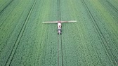 fertilizer field : Aerial view Farm machinery spraying chemicals on the large green field. Stock Footage