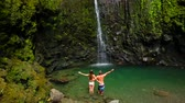 à beira da piscina : Attractive Young Couple Standing in a Shallow Pool Looking Up at a Waterfall in Hawaii