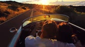casual : Happy Couple Driving on Country Road into the Sunset in Classic Vintage Sports Car. Steadicam Shot with Flare. Romantic Freedom Love Concept. Stock Footage