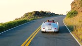 Happy Couple Driving on Country Road into the Sunset in Classic Vintage Sports Car. Cabriolet Steadicam Shot. Vídeos