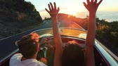 Couple driving convertible car. steadicam shot with flare into sunset in Hawaii Vídeos