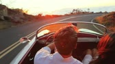 namorado : Happy Couple Driving on Country Road into the Sunset in Classic Vintage Sports Car. Steadicam Shot with Flare. Romantic Freedom Love Concept. Vídeos