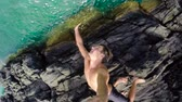 Extremely High Cliff Jump POV Young Man Backflips into Tropical Blue Ocean. Slow Motion.