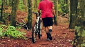 berendezés : Young Man Walking Mountain Bike Uphill on Forest Trail.  Outdoor Sports Healthy Lifestyle. Slow Follow Shot with Steadicam. Summer Extreme Sports.