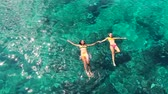 yüzme : Aerial View of Beautiful young women floating swimming in bikinis holding hands Stok Video