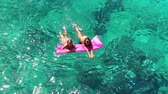 yüzme : Beautiful Young Women In Bikinis Floating on Pink Inflatable Raft in Crystal Ocean in Hawaii. Summer Fun Vacation Lifestyle. Diverse Ethnic Pacific Islander Hawiian Girl with Blonde Girl Friend.
