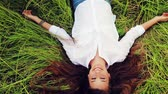 çayır : Beautiful Girl Lying on the Meadow and Dreaming. Enjoy Nature. Beautiful Brunette Blinks Open Eyes and Smiles
