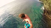 Young Man Jumps off Cliff Into Water. Summer Extreme Sports Outdoor Lifestyle.