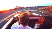 namorado : Happy Couple Driving on Country Road into the Sunset in Classic Vintage Sports Car