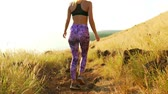 Young Athletic Woman Walking on Mountain Trail. Sunset Workout in Nature.
