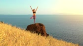 Young Woman Practicing Yoga in Nature. Reaching the Top. Mountian View at Sunset.