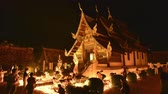 lanna : 4k, timelapse, Ton Kwen Temple, Chiangmai, Thailand 10 May, 2017: People light candles and pray at the Ton Kwen Temple on Visakha Bucha day. Noise and high ISO clip (Zoom-Out)