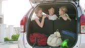 bagagem : happy children sitting in car at the day time. Concept of happy youth.