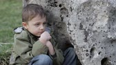 abuso : Sad little boy sitting near the big stone at the day time. Concept of sorrow. Stock Footage