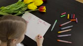 sorriso : Happy little girl makes a holiday card for his mom on the table.