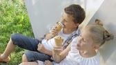 creme : Two happy children eating ice cream in the park at the day time. Concept healthy food. Vídeos