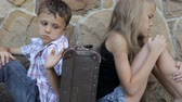 entediado : sad brother and sister are sitting by the wall with a suitcase at the day time