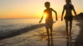 Happy children playing on the beach at the sunset time. Two kids having fun outdoors. Concept of summer vacation and friendly family. Vídeos