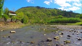 Beautiful view of river flows near village with green forest on the hill under sky with white clouds, Georgia, Guria