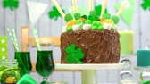 átomo : Happy St Patricks Day party table with chocolate cake decorated with cookies and candy, panning across up and down.