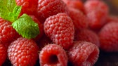paleo : Macro closeup of rotating summer fruit raspberries on wooden table.
