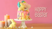 lolipop : On trend Easter candy land drip cake decorated with lollipops, cand eggs and white chocolate bunny in party table setting, with animated text greeting.