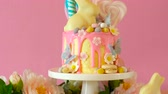 temas animais : On trend Easter candy land drip cake decorated with lollipops, cand eggs and white chocolate bunny in pink party table setting.