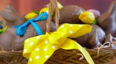 Happy Easter hamper of chocolate eggs and bunny rabbits in large basket with silk tulips on dark wood table, dolly reveal macro.
