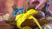 Happy Easter hamper of chocolate eggs and bunny rabbits in large basket with silk tulips on dark wood table, stacking eggs timelapse.