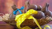 水玉模様 : Happy Easter hamper of chocolate eggs and bunny rabbits in large basket with silk tulips on dark wood table, stacking eggs. 動画素材