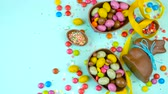 здесь : Happy Easter decadent chocolate background overhead with Easter eggs and candy on a rustic wood background with copy space.