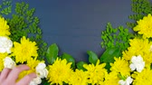 Easter springtime overhead flat lay display of fresh flowers on dark blue wood table background, time lapse.