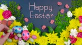 Easter springtime overhead flat lay display of fresh flowers on dark blue wood table background, with animated text.
