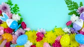 Easter springtime overhead flat lay display of fresh flowers on blue wood table backgound, real time.