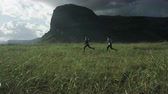 northern hemisphere : Man and woman playfully running through field